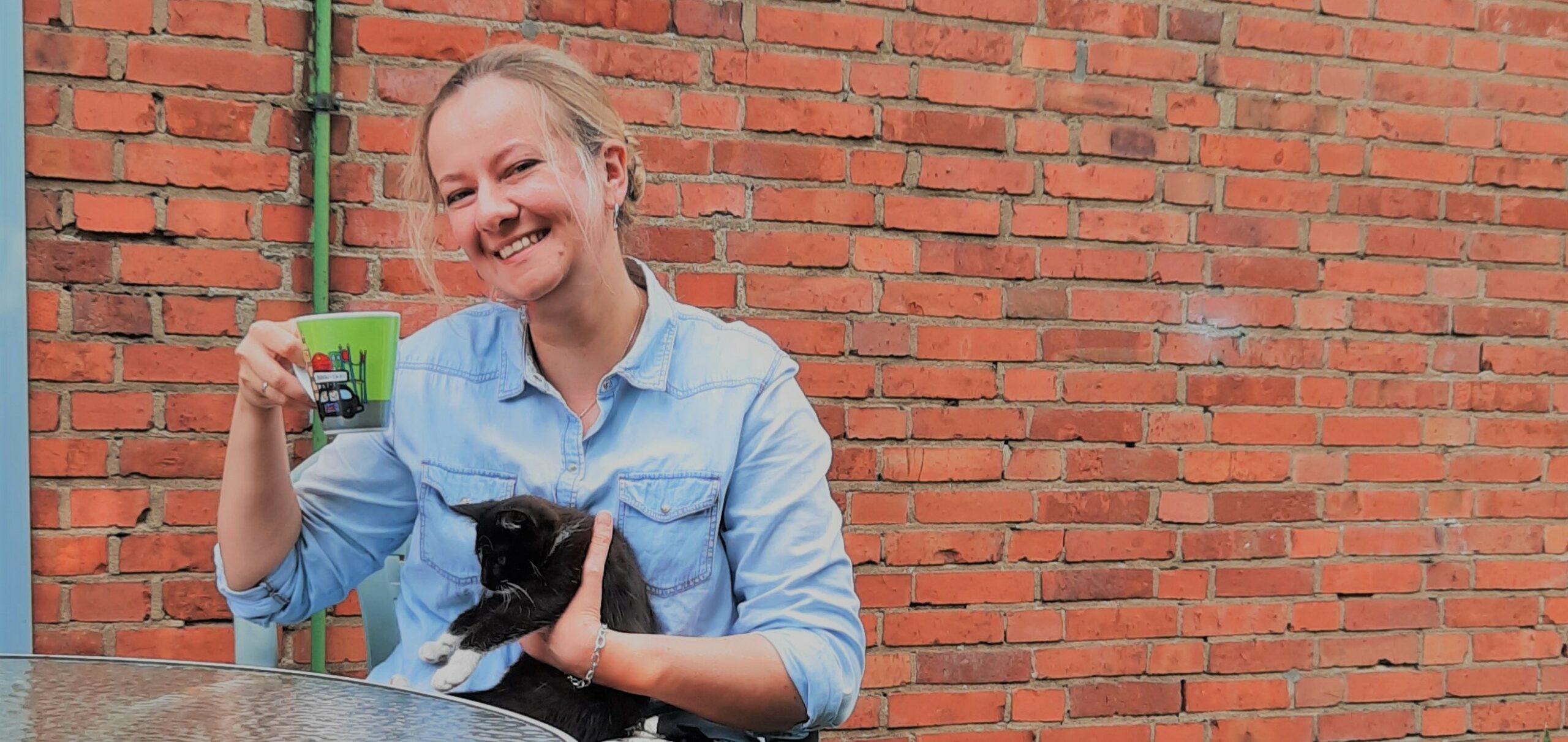 Frau Tomma Theophil sitzt vor Backsteinwand lächelt Kaffeetasse in der rechten Hand schwarze Katze auf dem schoß